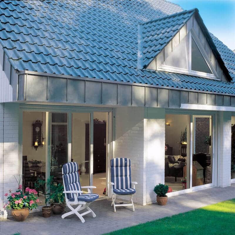 Haus mit weißen Fenstern und Terrasse