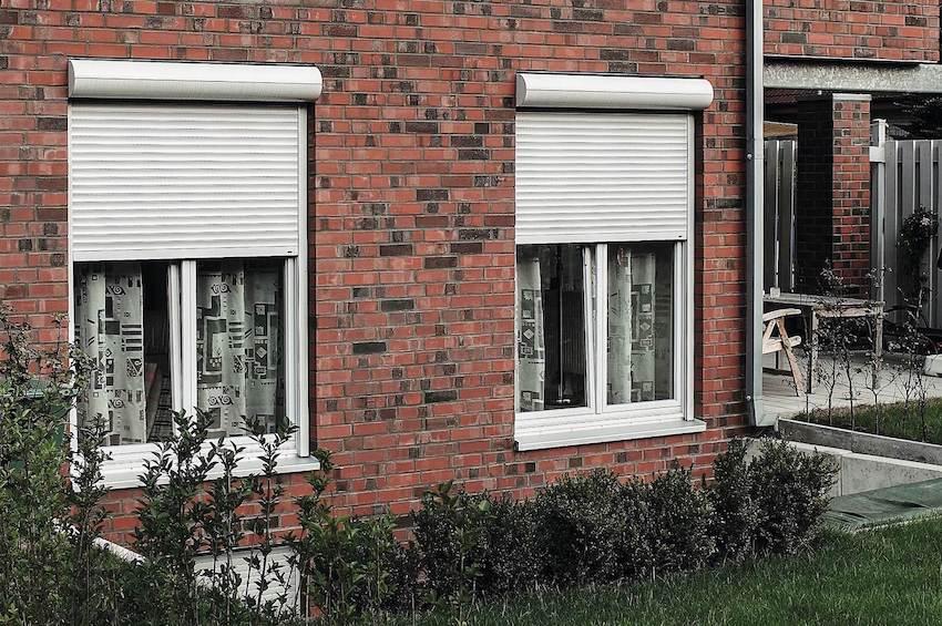 Weißes modernes kastenförmiges Haus mit grauen Fenstern und Rollläden